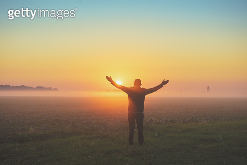 Happy man with hands in the air stands in the field early in the morning and enjoying the sunrise