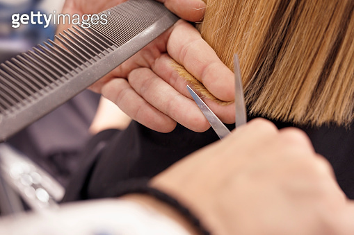 Hairdresser in action  Hair Cutting.  Natural Beauty  woman at a hair salon