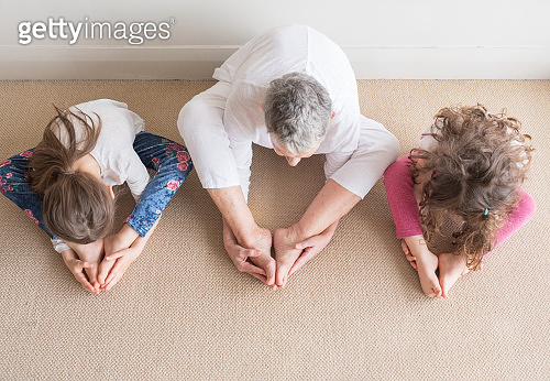 Older woman with young children in yoga stretch posture from above