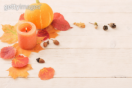candle with autumn leaves on white wooden background