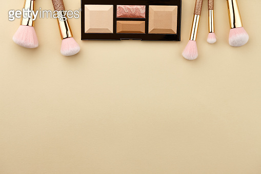 Make up palette and brushes on beige background