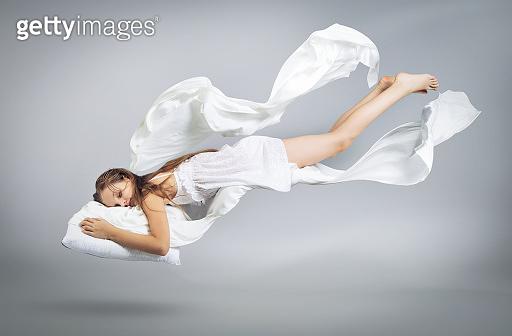 Sleeping girl. Flight in a dream. White linen flies through the air.