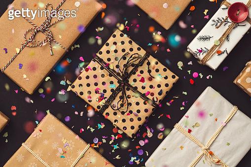 Gift box flat lay under confetti rain on black background