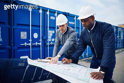 Engineers discussing blueprints while working in a commercial shipping yard
