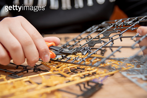 A boy's hand assembling plastic models using tools.
