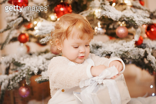Family on Christmas morning. Baby girl opening Xmas presents. Children under Christmas tree with gift boxes. Decorated living room with christmas toys. Cozy warm winter day at white home.