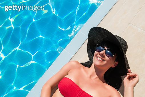 Beautiful tanned woman in red bikini relaxing near luxury swimming pool.