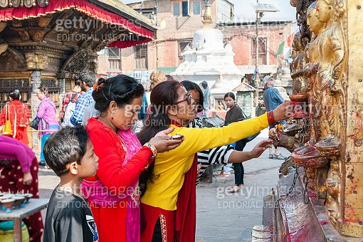 Women pray at the Swayambhunath temple in Kathmandu, Nepal