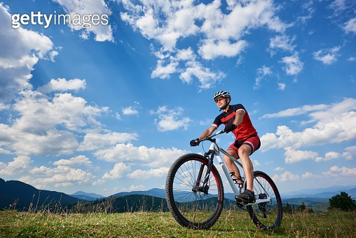 Athletic professional sportsman cyclist in sportswear and helmet cycling cross country bike