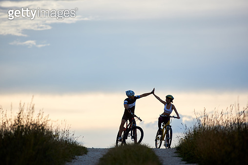 Silhouettes of sportsmen riding bicycles and highing five.