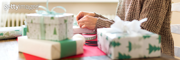 DIY Gift Wrapping Banner. Unrecognisable woman wrapping beautiful nordic style christmas gifts. Hands close up.