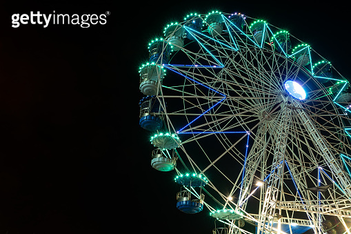 Colourful striped light illuminated spinning ferris wheel in motion moving at night.
