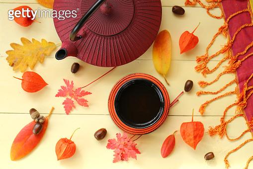 Autumn tea drinking. burgundy textured teapot in Asian style,cup of tea, physalis, yellow leaves, acorn on yellow wooden background.Autumn season.