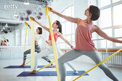 Photo of strong healthy woman practicing yoga exerciese on fitness mat in white sport class. Adult fit female doing stretching early morning indoor on background people