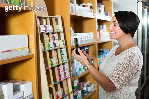 Glad mature female customer holding mobile phone
