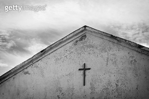 Black and white photo of the cross on the roof of the old church