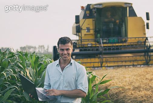 Engineer standing in field with combine harvester in background
