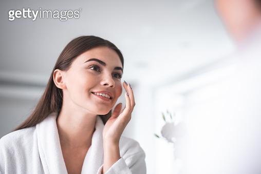 Satisfied woman applying cream on face indoor