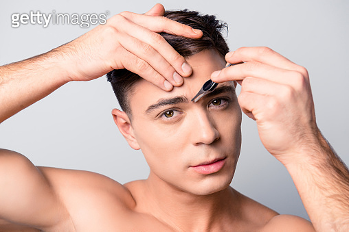 Cropped close up portrait of handsome concentrated confident muscular man plucking the area between his eyebrows using tweezers, isolated on grey background