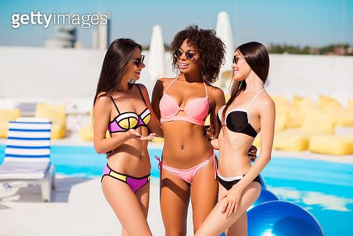 Three beautiful sexy sexual slim slender charming excited carefree relaxed stylish joy enjoy fun attractive pretty hot girls in colorful bikini having conversation near swimming pool sunshine