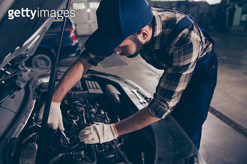 Close up of young bearded expert specialist appraising the damage for repairing car at work shop, mounting it, arms in white knitted gloves, hat and special blue uniform overall, ckeckered shirt