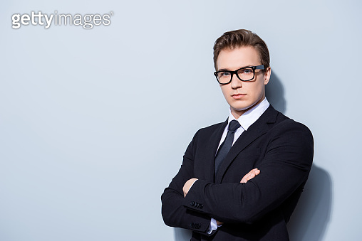 Successful young handsome man lawyer in a suit and glasses on pure background with crossed hands. Severe and harsh, rich and confident, attractive and smart