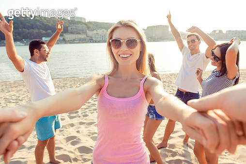 Attractive smiling girl dancing with her boyfriend on beach party