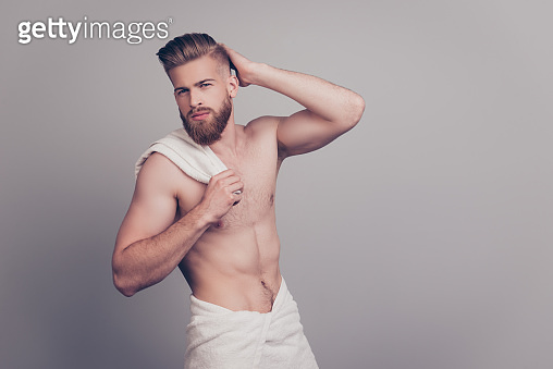Balm lotion cream wax. Portrait of masculine handsome groomed neat sexy attractive confident macho looking in mirror correcting fixing furfur white towel on hips isolated on gray background copy-space