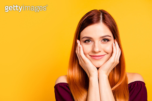 Portrait of red straight-haired attractive cute nice happy smiling young girl, hands touching cheeks. Copy space. Isolated over bright vivid yellow background