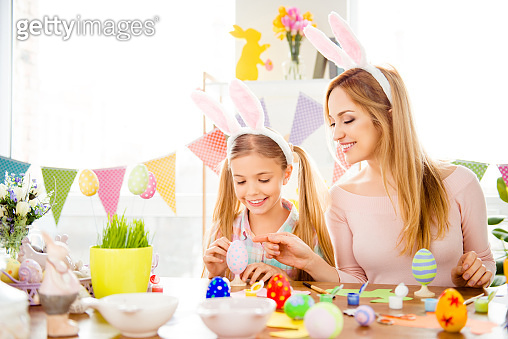 Happy Easter atmosphere! Funny, pretty, creative mom teaching, explain, to her cute, small, joyful daughter how to draw, paint, decorate easter eggs, together wearing bunny ears, sitting at desk