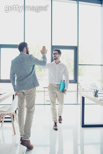 Full size of two handsome brunet guys colleagues, dressed classy and elegant, are giving high five while passing each other in office, successful friendly men