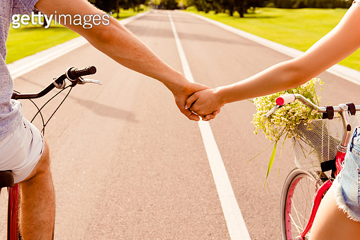 Close up photo of man and woman holding hands while cycling