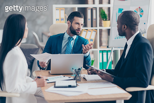 Attractive, handsome, stylish, elegant man in classic suit explaining something to his partners, three colleagues sitting in workstation, solving problems, finding solution, expertising results