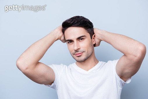 Confident smiling handsome young man in white t shirt. standing on the pure background, fixing his perfect hairstyle. So hot and attractive, harsh and fashionable
