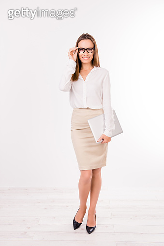 Full size portrait of caucasian feminine charming lovely cute expert business lady in smart outfit, standing on pure white background with digital pda, beaming smile, adjusts her black specs