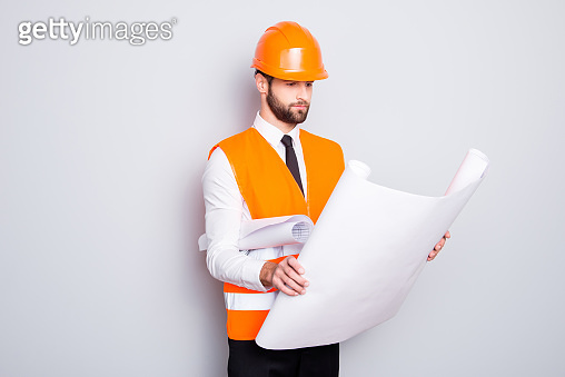 Portrait of busy handsome concentrated architect in shirt, tie and hard hat, expertising scheme of building, having open paper roll in hand, isolated on grey background