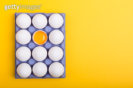 White eggs and egg yolk on the yellow background with copy space