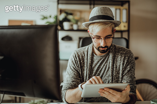 Young hipster using his digital tablet in the office during morning hours