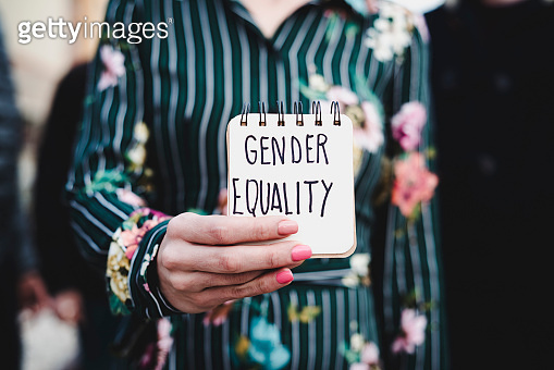 woman shows notepad with the text gender equality
