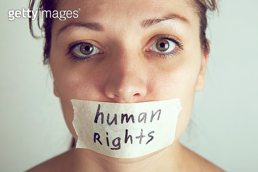 Woman with wrapping her mouth by adhesive tape. International Human Right day