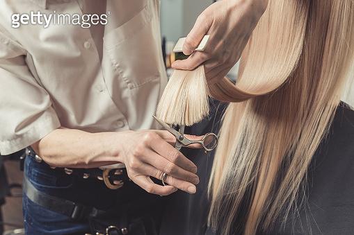 Hairdresser is cutting long hair in hair salon