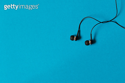 Portable small black earphones. Isolated on blue background. Empty text space