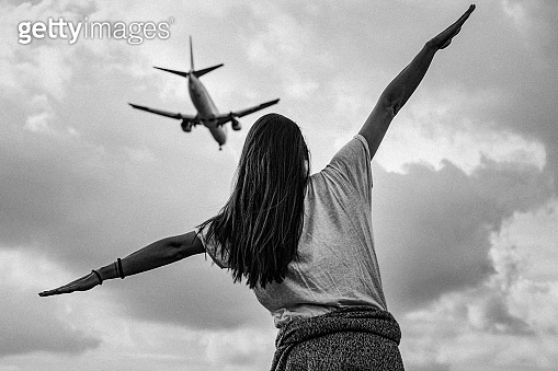 Rear view of a young woman with outstretched arms imitating flying commercial airplane above her