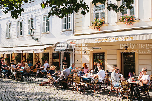 A popular street cafe near the Charles Bridge. Local residents and tourists rest, eat and communicate on a sunny warm day.