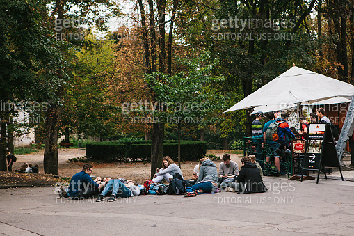 Prague, September 25, 2017: A group of young friends of students lies and sits on the ground and communicates with each other. Rest together. Urban lifestyle and positive emotions.