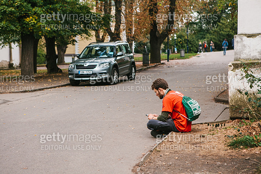 Prague, September 25, 2017: A young tourist guy with a backpack is sitting on the street and communicating with a smartphone with friends.