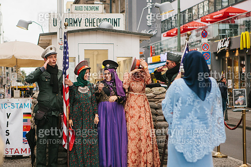 Positive peaceful cheerful beautiful Arab women in traditional costumes communicate and take pictures with American soldiers next to checkpoint Charlie