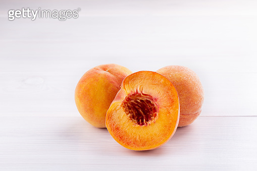Ripe peaches close-up on a white wooden background.