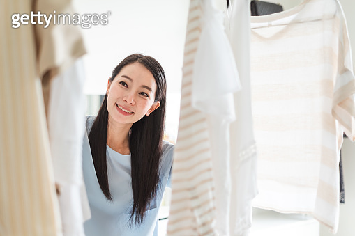 Asian woman choosing clothes in wardrobe, dressing lifestyle concept