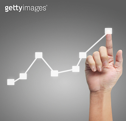 Hand touching graphs of financial indicator